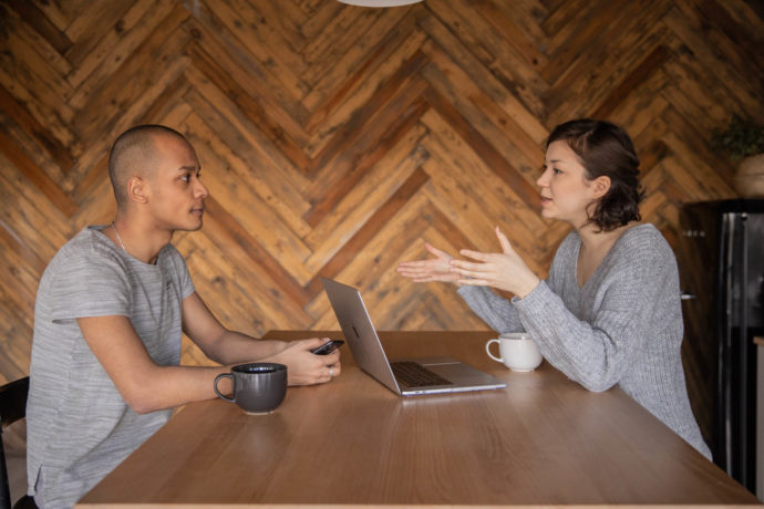 Two people having a discussion at a table.