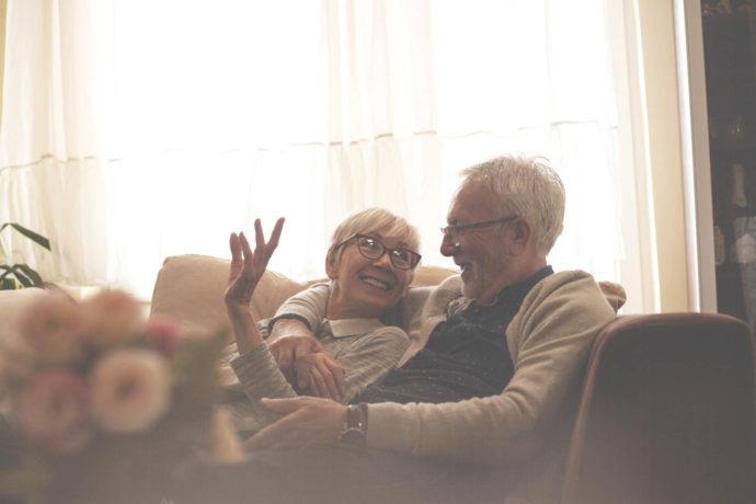 Senior couple resting on sofa,watching tv.