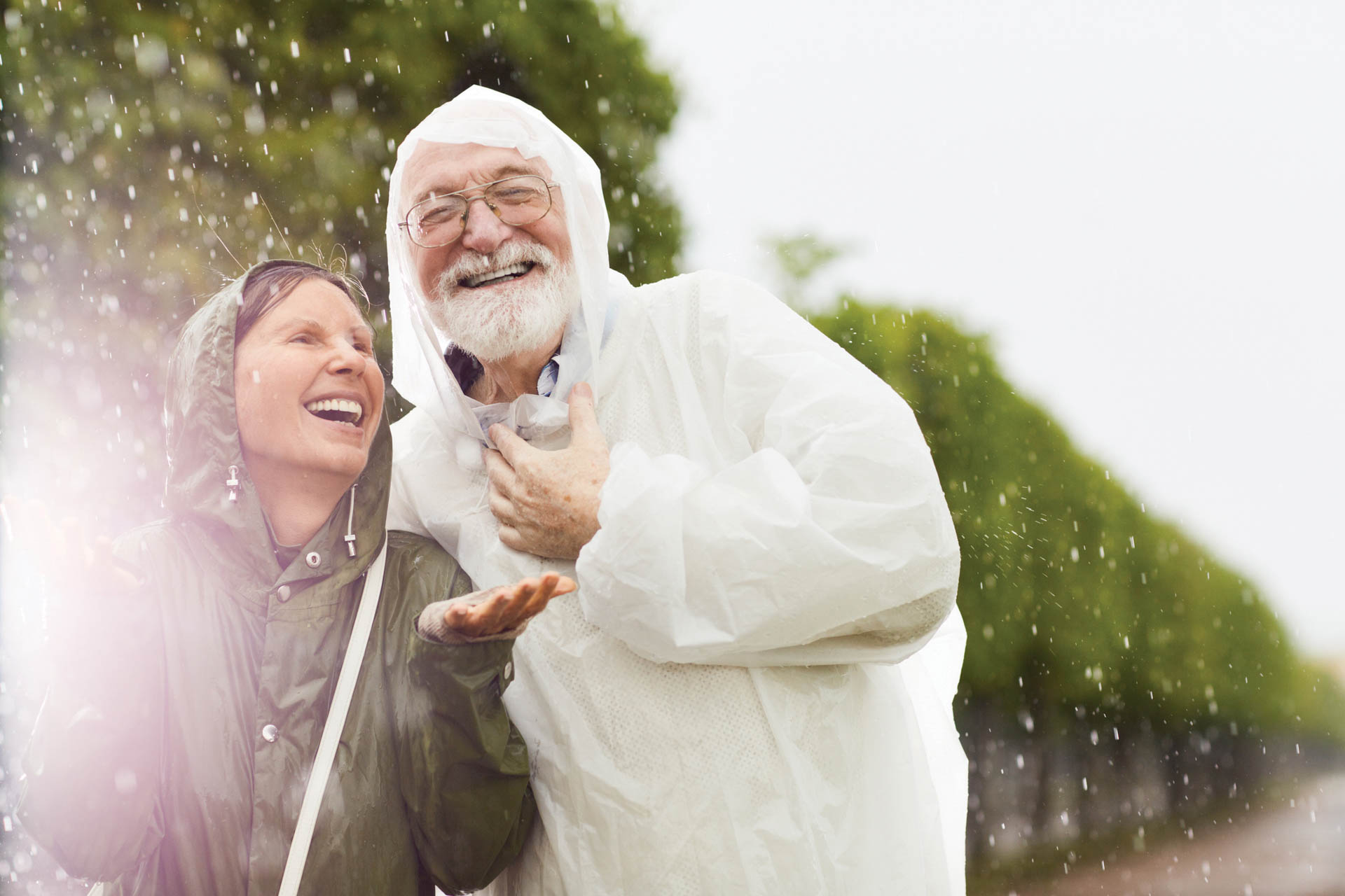 Cheerful aged woman catching raindrops on palms with her laughing husband near by.