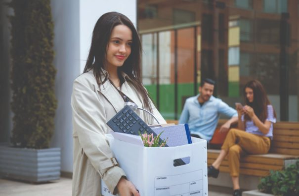 Woman carrying a box of work supplies.