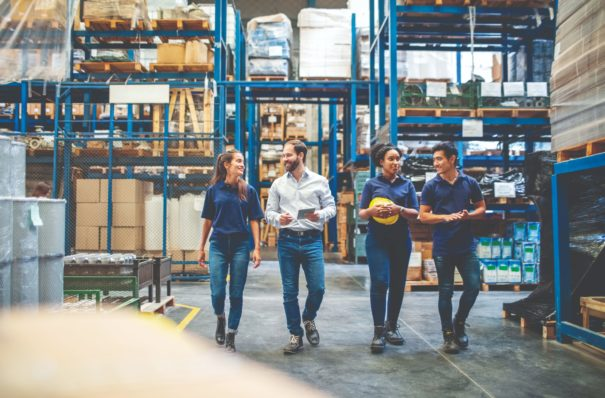 Workers walking through a warehouse.