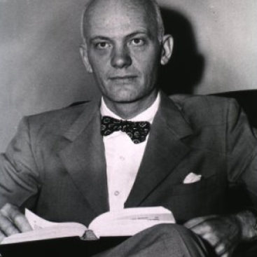 Vintage photo of a man with a bowtie reading a book.