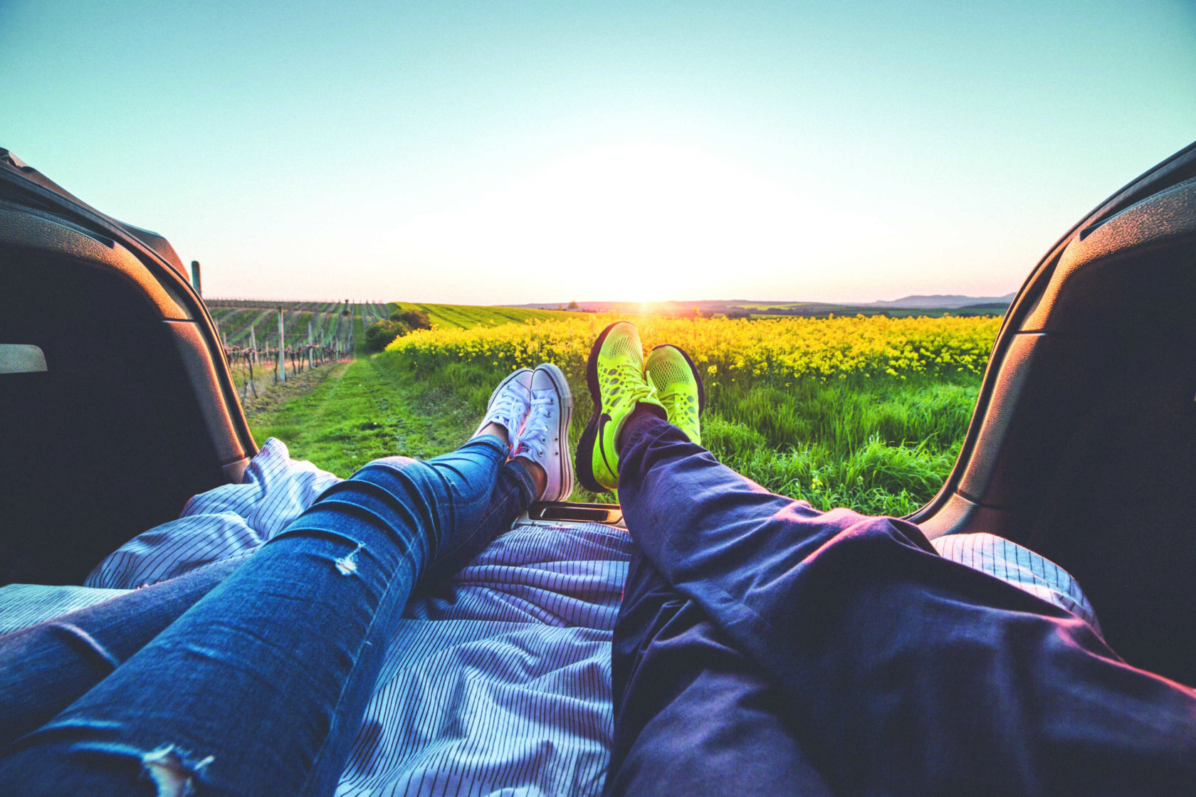 Two people laying down in the trunk of a car looking out at a field of flowers.