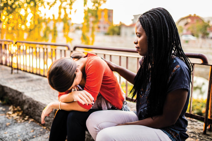 Woman consoling another woman on a bench outside.