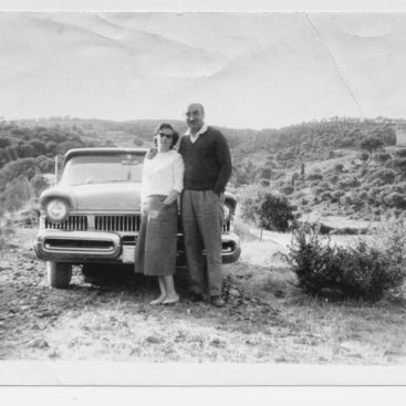 A couple standing in front of their car from the 1950s.