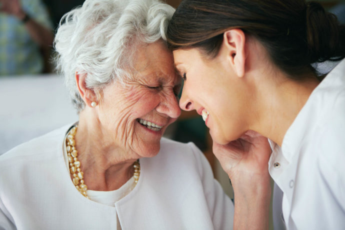 Senior mother and adult daughter smiling with heads together.