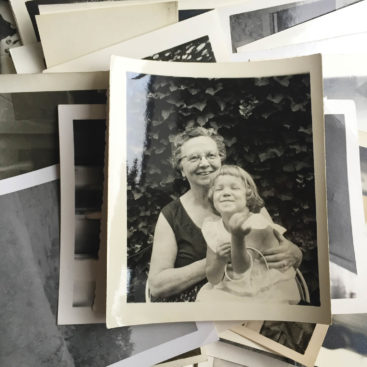 Pile of old black and white photographs.